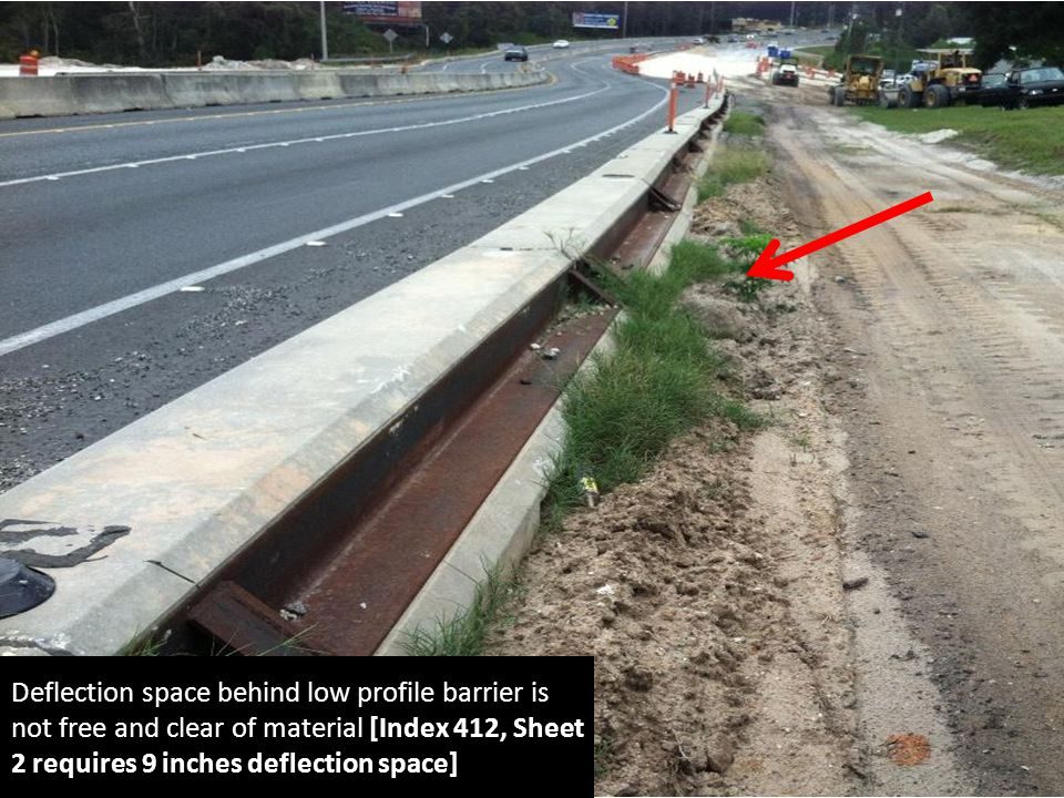 Deflection space behind low profile barrier is not free and clear of material [Index 412, Sheet 2 requires 9 inches deflection space]